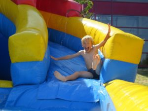 Barracudas Day Camp Child laughing whilst sliding down an inflatable water slide